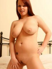 Pictures of busty redhead Rubi stripping to show her incredibly curvy body