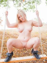 Curvy blonde girl Marilyn shows you her tits and pussy on the swing