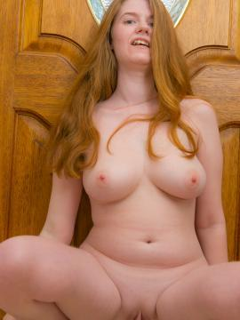 Curvy redhead Andriel strips completely naked by the door