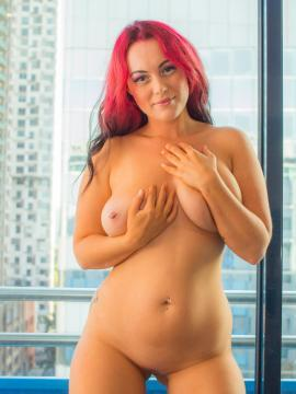 Pretty redhead Chikita strips nude in her first set