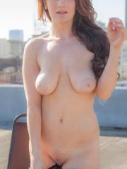 Busty model Emmy Sinclair strips for you on the rooftop