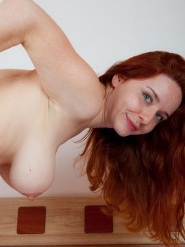 Busty redhead Sara Nikol strips out of her lingerie in bed