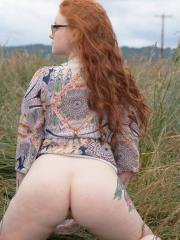Busty redhead Kaycee Barns gets naked in the field