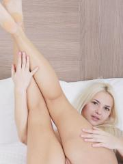 Leonie relaxes on bed and spreads her smooth legs wide open to reveal her pink pussy