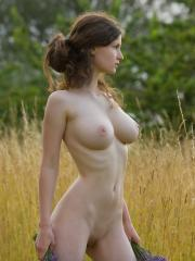 Pictures of busty girl Susann getting naked in the field