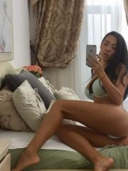 Brunette teen Kimber Leen uses her camera phone in bed