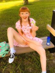 Redhead teen Krystal Orchid lifts her dress to play with her pussy at a park