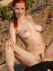 Pictures of redhead girl Ariel A naked and spreading her legs outside