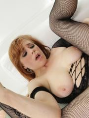 Busty redhead Penny Pax practices with a huge dildo before taking the real thing