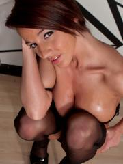 Busty babe Nikki oils up her big boobies while wearing sexy black stockings