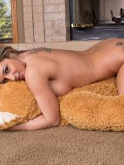 Busty beauty Nikki Sims shows off her long legs in with a giant teddy bear