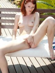 Gorgeous redhead Mia Sollis strips naked and touches herself outside