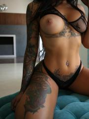 Busty tattooed brunette babe shows off her big boobs for you